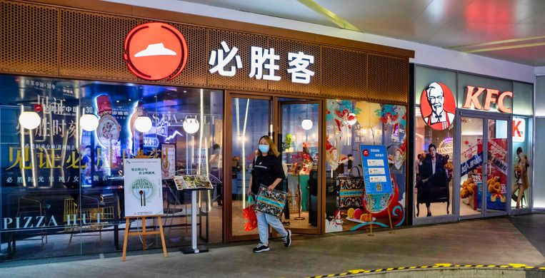 Een vrouw passeert restaurants van Pizza Hut en KFC in Shanghai, China. De Chinezen zijn nog huiverig om geld uit te geven.  De eerste acht maanden van dit jaar gaven ze 26 procent minder uit aan eten en drinken, dan in dezelfde periode vorig jaar. Beeld EPA, Alex Plavevski