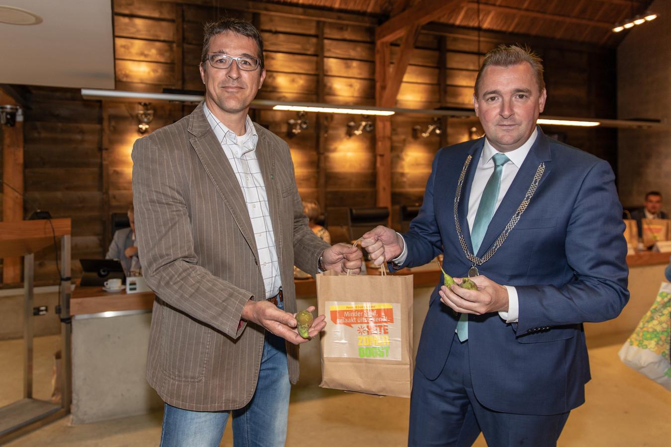 CDA-fractievoorzitter Peter van 't Westeinde overhandigt burgemeester Gerben Dijksterhuis van Borsele een tasje met kleine peren.