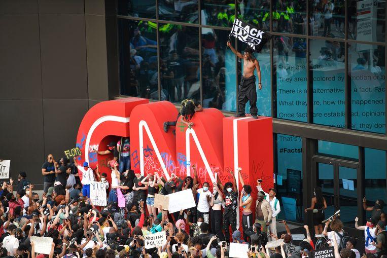 Betogers beklimmen het CNN-logo bij het hoofdgebouw van de tv-zender in Atlanta. Beeld AP