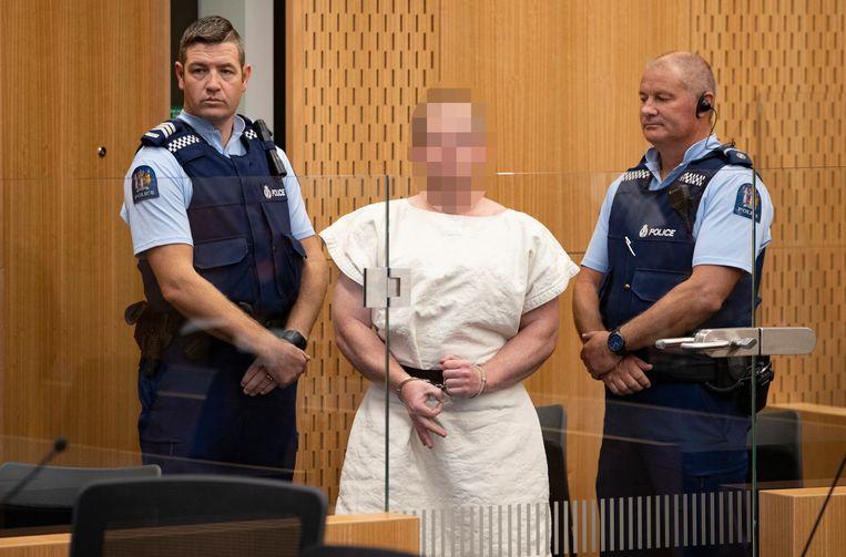 Het gezicht van de verdachte van de moordaanslag in Christchurch, Nieuw-Zeeland, is geblurd. Met zijn handen maakt bij een gebaar naar de camera. Beeld EPA