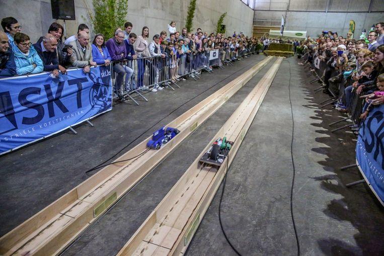 Het publiek vergaapt zich aan de racebaan waar de machines het tegen elkaar opnemen.