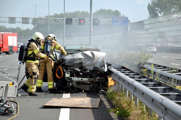De brandweer blust de in brand gevlogen auto op de A12 in Arnhem.