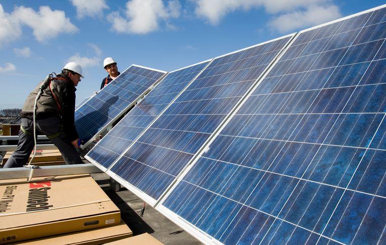 Zonnepanelen worden aangelegd op het dak van een huis. Beeld ANP XTRA