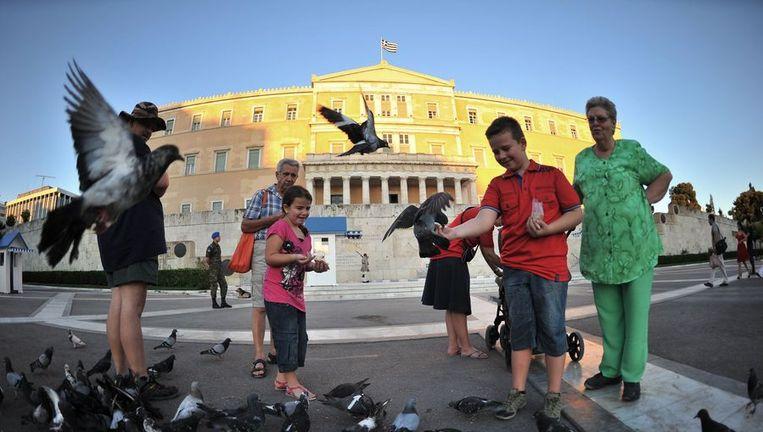 Toeristen voor het Griekse parlement in Athene. Beeld null