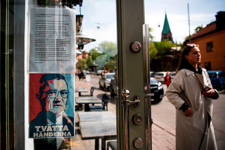 Een portret van Anders Tegnell roept op je handen te wassen, bij een restaurant in Stockholm. Beeld AFP