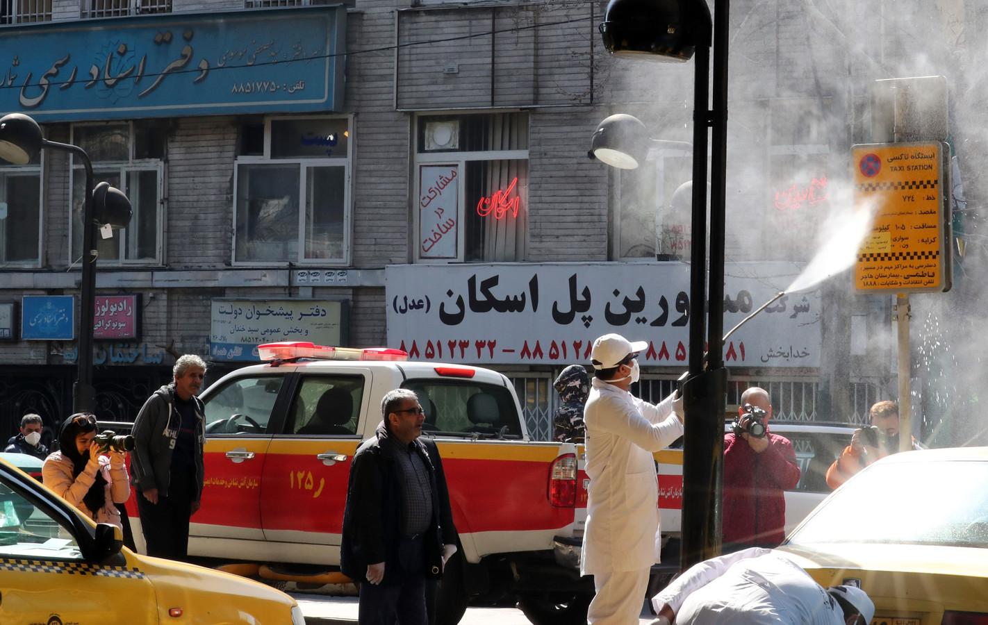 Een gemeentearbeider desinfecteert met een spuit een bord in het straatbeeld van Teheran. Volgens Iraanse artsen heeft de regering de uitbraak van het coronavirus ernstig onderschat.