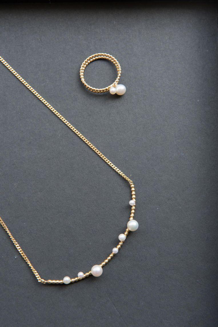 Een gouden ketting met parels met bijhorende ring.