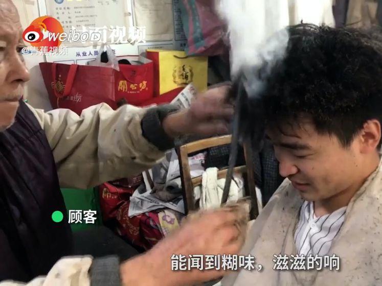 91-jarige kapper schroeit de haren van zijn klanten met gloeiende metalen staaf