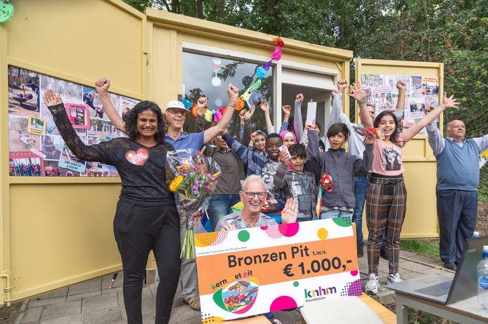 De initiatiefnemers van Gewoon Buiten, met links Renuka de Kunder en zittend met de cheque Theo Weenink, zijn heel blij met de Bronzen Pit.