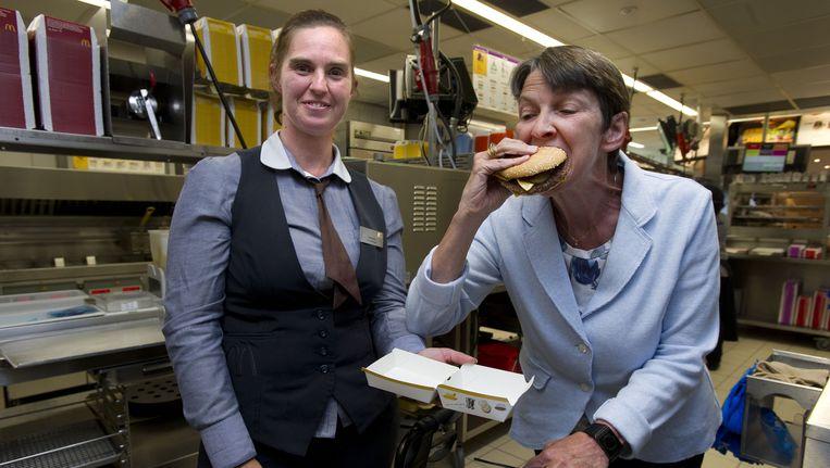 Minister Klijnsma neemt een hap uit een hamburger tijdens een van haar werkbezoeken aan bedrijven met werknemers die een arbeidsbeperking hebben. Beeld null