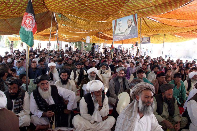 Afghanen luisteren naar kandidaat Mir Wali, in Helmand, Afghanistan.