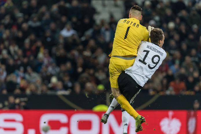 De Duitse aanvaller Luca Waldschmidt krijgt een flinke opdoffer in het duel met doelman Aleksandr Gutor van Wit-Rusland.