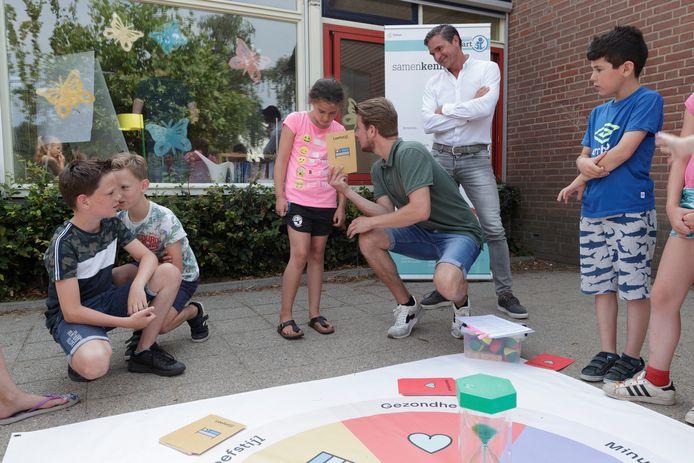 Bedenker van het spel, David Jordens (gehurkt), geeft uitleg over het spel aan de kinderen. Voormalig schaatskampioen Hein Vergeer (witte blouse) kijkt toe.