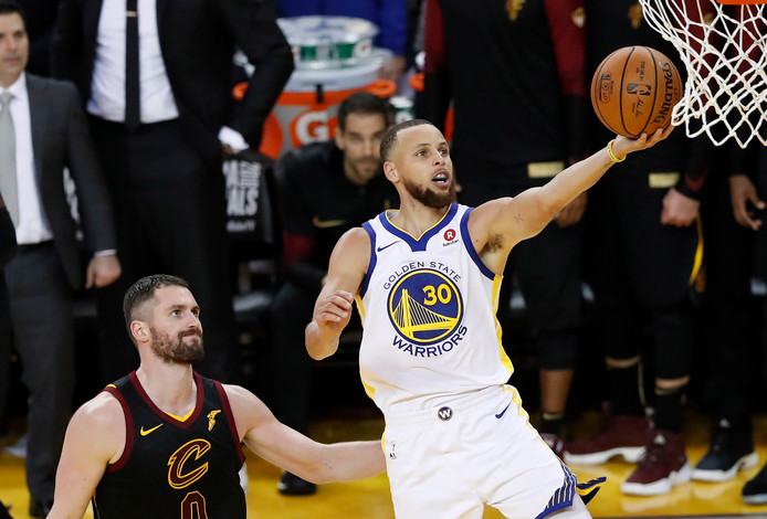 Stephen Curry (rechts) van de Golden Staten Warriors gaat langs center Kevin Love van de Cleveland Cavaliers en scoort in Game 1 van de NBA Finals.