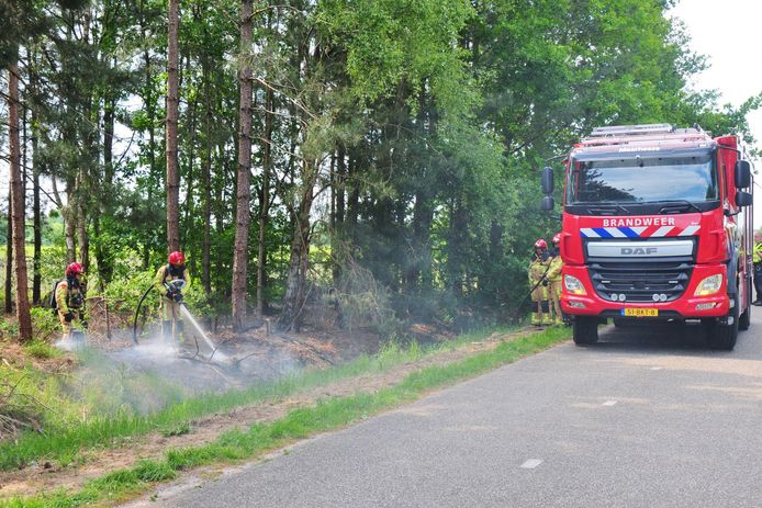 Brandweer blust beginnende natuurbrand in berm van ventweg naast snelweg A2 bij Maarheeze.