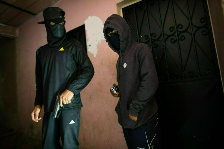 """Twee gemaskerde criminelen uit Caracas, die deze week poseerden voor een fotograaf van Associated Press. """"Als je je magazijn leegschiet ben je zo vijftien dollar kwijt."""" Beeld AP"""