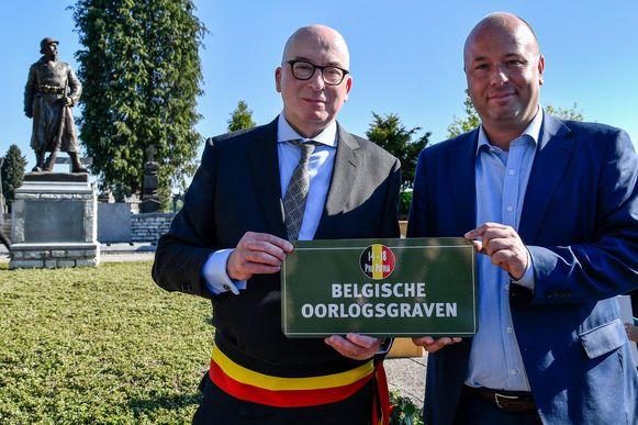 Piet Buyse en Franky Bostyn met het gedenkplaatje op de begraafplaats in Appels.