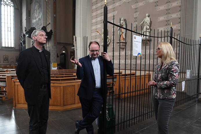 Madeleine van Toorenburg krijgt in de Elisabethkerk uitleg van pastoor René Aarden en Alex van Megen.