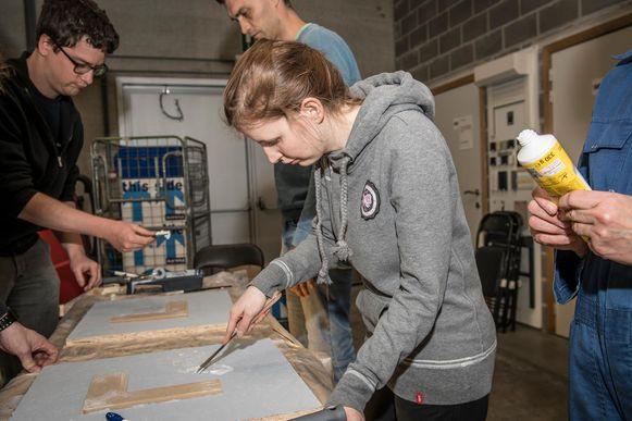Enkele jongeren aan het werk tijdens de workshop meubels restaureren.
