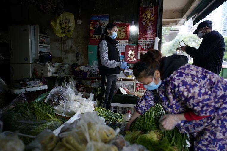 Winkels in Wuhan worden aangemoedigd weer open te gaan, maar klanten aan de deur te bedienen. Beeld REUTERS