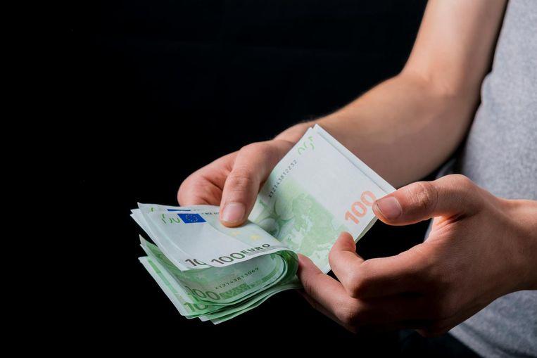 Een vrouw telt briefjes van honderd euro.