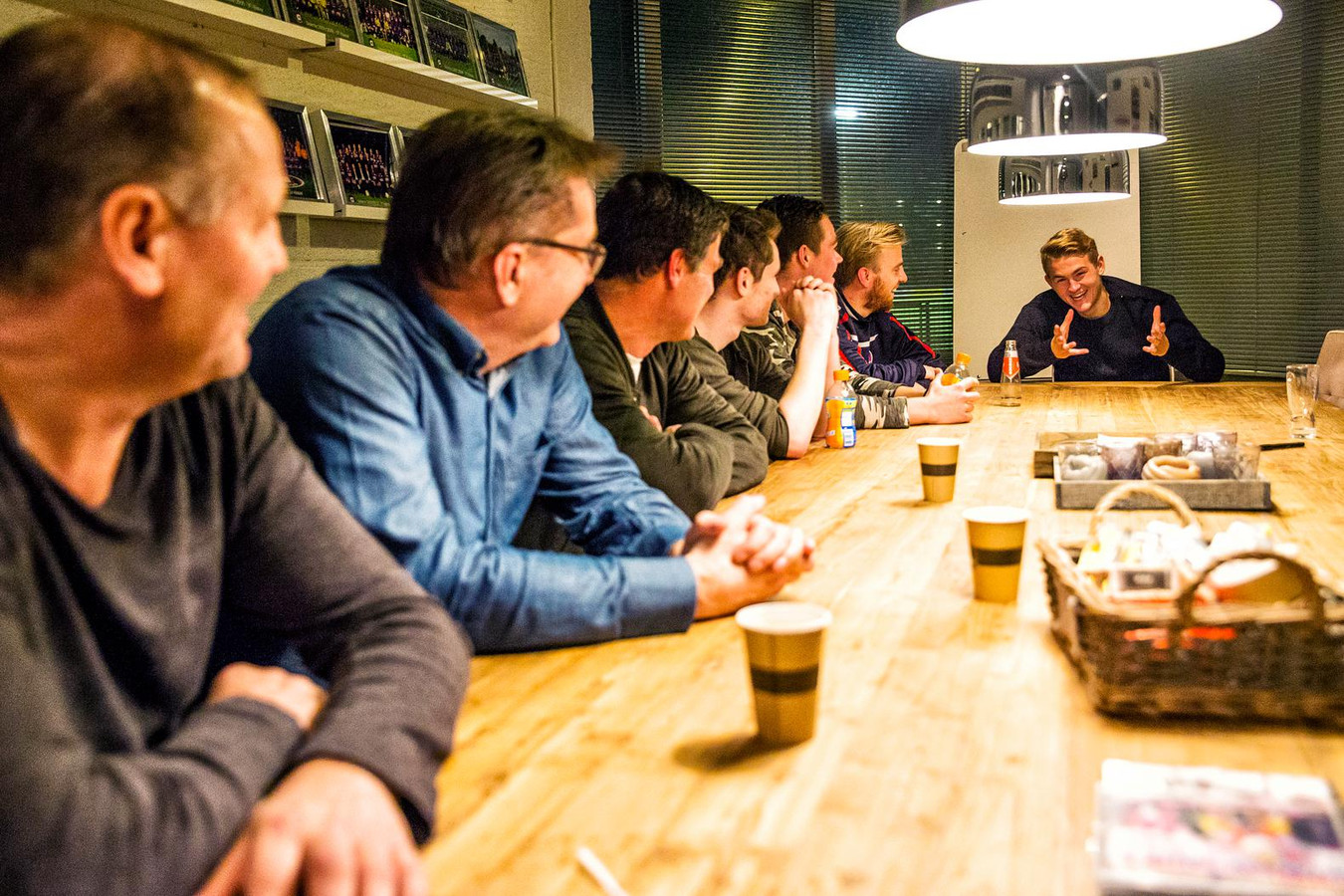 Matthijs als stralend middelpunt aan de vergadertafel met oud-trainers, vrienden en met vader Frank (met bril).