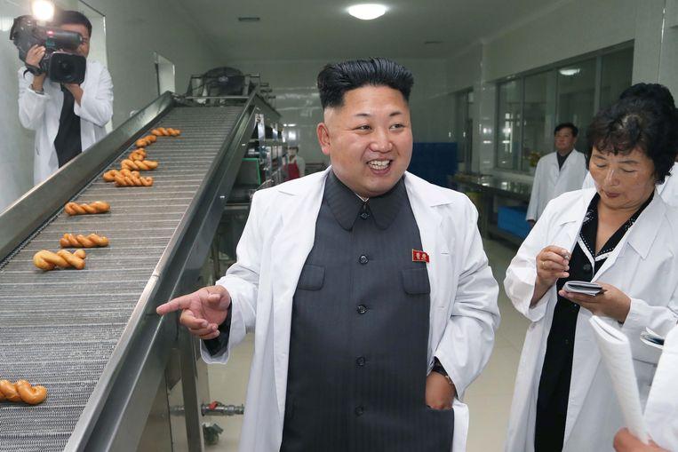 De Noord-Koreaanse leider Kim Jong-un in een fabriek van het leger die voedsel produceert voor de militairen. Beeld null