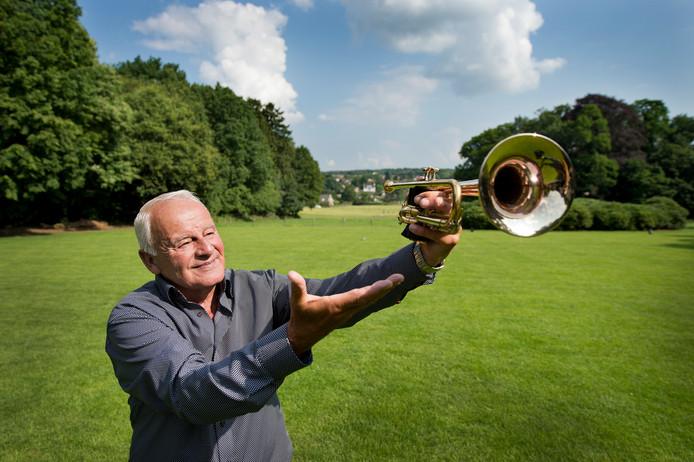 Leo Wijnhoven met zijn trompet op het terras van De Wolfsberg.  Groesbeek gloort in de verte.