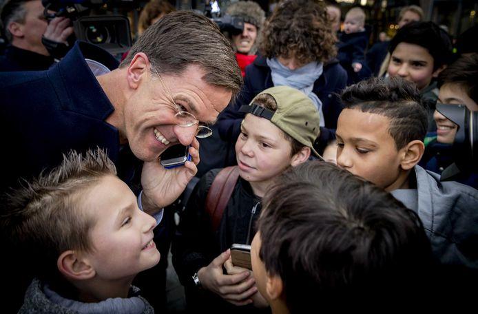 Rutte belt tijdens een eerdere campagne met de moeder van een jongetje, in aanloop naar de Tweede Kamerverkiezingen.