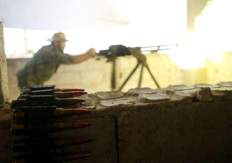 Koerdische strijder van de Volksbeschermingseenheden (YPG) vuurt met een zwaar machinegeweer naar militanten van IS in Raqqa, in juni vorig jaar.