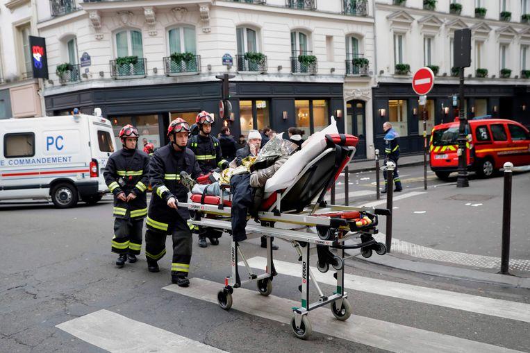 Brandweermannen voeren een gewonde af.