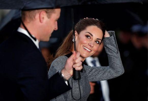 William en zijn vrouw, Kate, schuilen samen onder een paraplu.