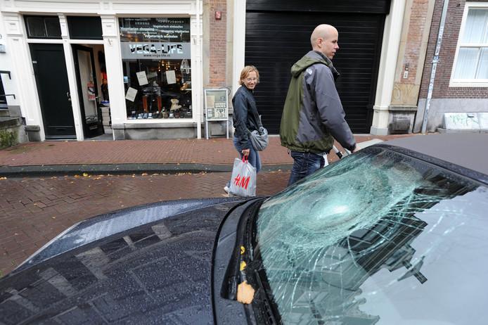 Een zwaar beschadigde voorruit van een Porsche, die staat geparkeerd langs een gracht in de Amsterdamse binnenstad.
