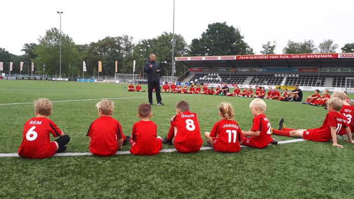 De deelnemers aan het FC Twente Soccer Camp bij ATC luisteren naar de instructies van trainer Dennis van Toor.
