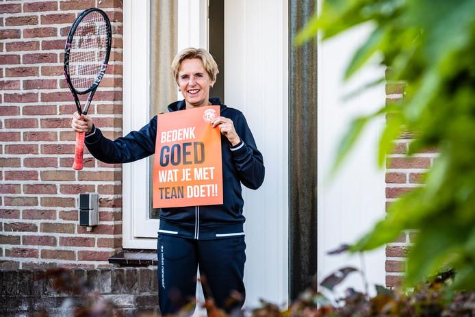 TEAN-lid Carin Kleiweg met de actieposter van haar tennisclub. Ze woont tegenover politicus André de Jeu en heeft daarom haar bovenraam volgehangen met posters.