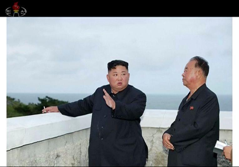 De Noord-Koreaanse leider Kim Jong-un (l) kijkt naar het testen van een nieuw wapensysteem. Beeld null