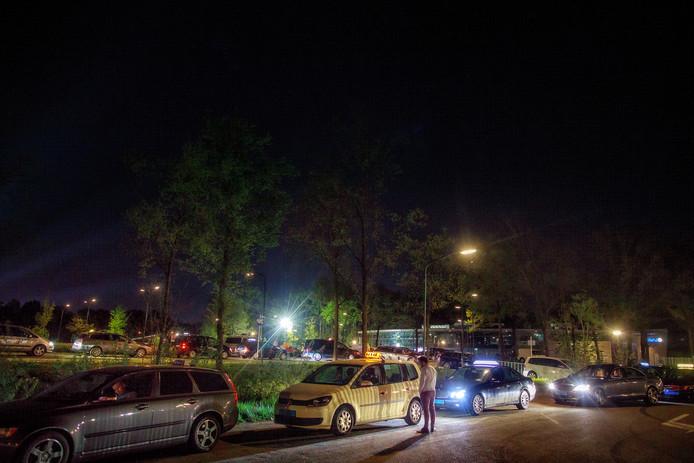 Rijen taxi's wachten op het parkeerterrein bij het zwembad in Schijndel op de festivalgangers van Paaspop. Het leidt tot de nodige frustraties en taxistress.