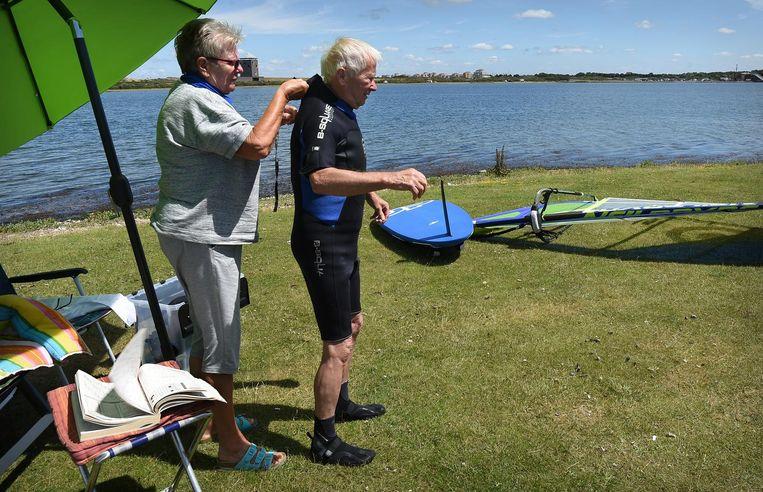 Een surfer van 82 jaar wordt door zijn vrouw geholpen met het aantrekken van zijn surfpak. Beeld null