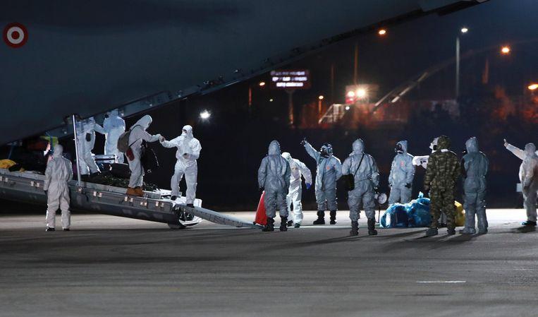 Verschillende groepen evacués worden uit Wuhan naar Europa vervoerd. Beeld AP