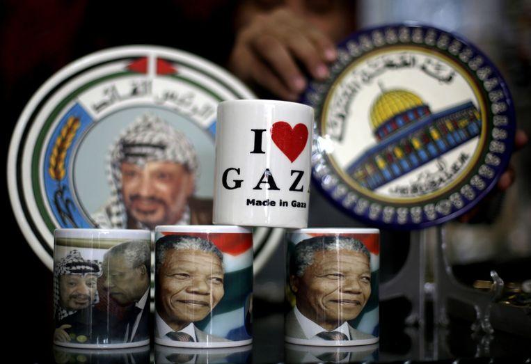 'Onze vrijheid is onvolledig zonder de vrijheid van de Palestijnen', zei Nelson Mandela in 1997. Vergelijkingen met de Zuid-Afrikaanse apartheid werden al langer gemaakt, en hevig betwist door Israël, maar zeker sinds die uitspraak zien veel Palestijnen de strijd van de zwarte Afrikanen voor gelijke rechten als een voorbeeld. De spullen op de foto stonden in een winkel in Gaza-stad, vlak na de dood van Mandela in 2013. Beeld Mohammed Abed / AFP