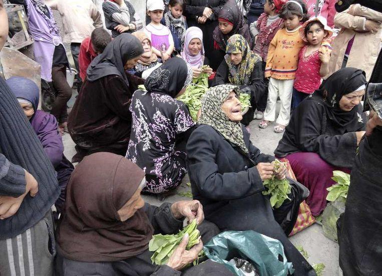 Voedsel wordt uitgedeeld in een Palestijns vluchtelingenkamp ten zuiden van Damascus. Beeld reuters
