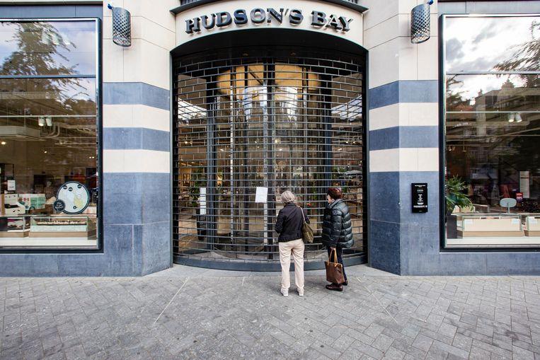 Voorbijgangers staan donderdag voor een gesloten Hudson's Bay-filiaal aan het Rokin. Beeld Maarten Brante
