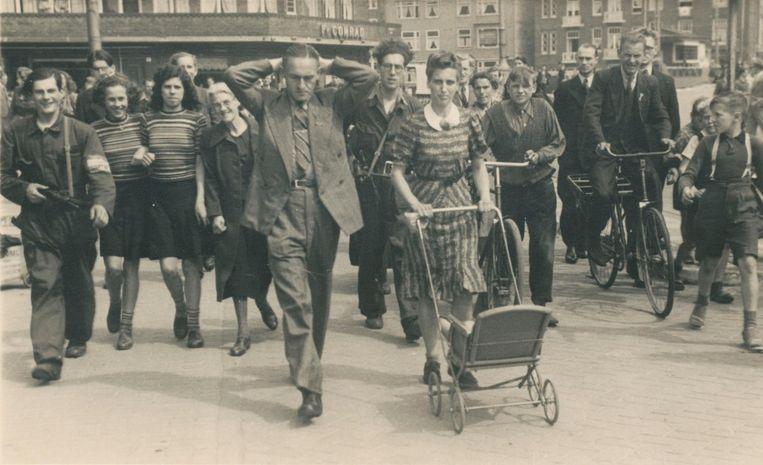 ¿ Op de hoek van de Witte de Withstraat en de Postjesweg werd mei 1945 een 'fout' stel door twee gewapende BS'ers weggevoerd. De kinderwagen was leeg. Hun kind was reeds naar een opvangadres gebracht. Het leedvermaak onder buurtgenoten bij de arrestatie van 'moffenvrienden' was groot Beeld J.W.Hofman/BBWO2/NIOD