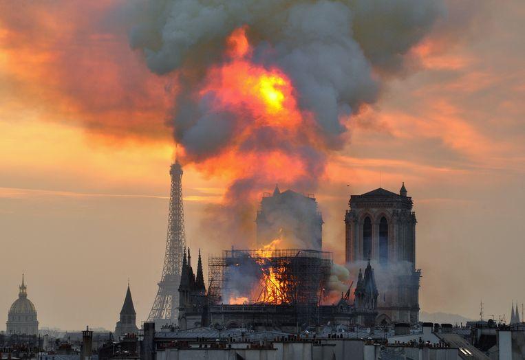 Vlammen slaan uit het dak van de Notre-Dame. Beeld AP