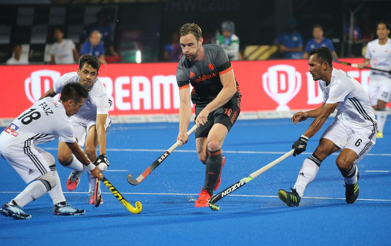 Mirco Pruyser wordt omsingeld door drie Maleisiërs op het WK hockey in India. De spits van het Nederlands elftal scoorde een keer.  Beeld EPA