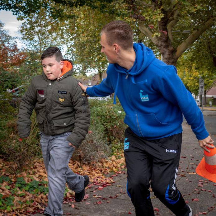Lucas Herrings van de F!TFabriek  in actie met één van de  leerlingen van Het Kompas die twee rondjes rond de school rennen.