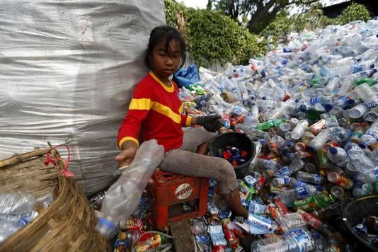 Een meisje sorteert afval in Indonesië.