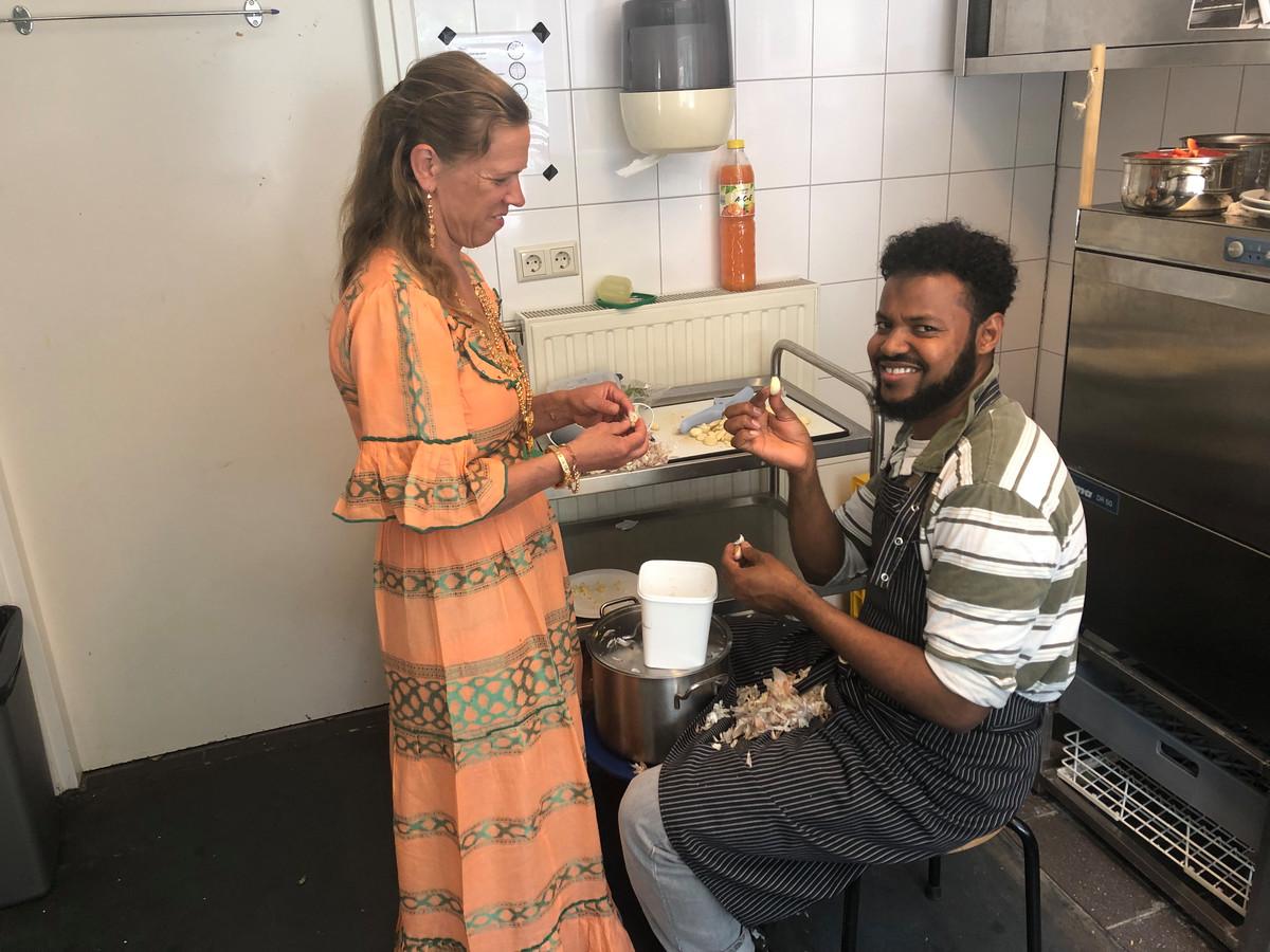 Sandra Geertse helpt Abdourezak Ahmed Hussein in de keuken bij de bereiding van de maaltijd.