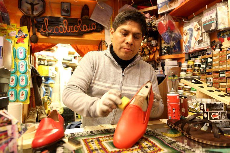 De schoenmaker van Benedictus, Antonio Arellano, poseert met de pauselijke rode schoenen Beeld getty