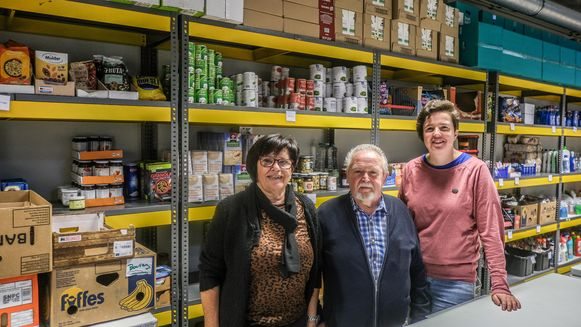 Vrijwilligers Marleen en Albert samen met schepen Eva Ryde in de loods van de voedselbedeling.